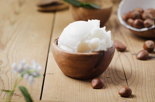 Shea butter in wooden bowl with nuts on old rustic table. Free text space.